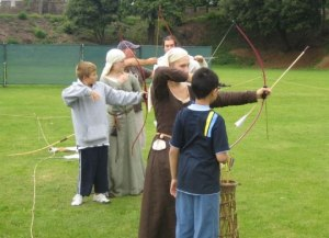 Several members teach have-a-go archery to the public at a show.
